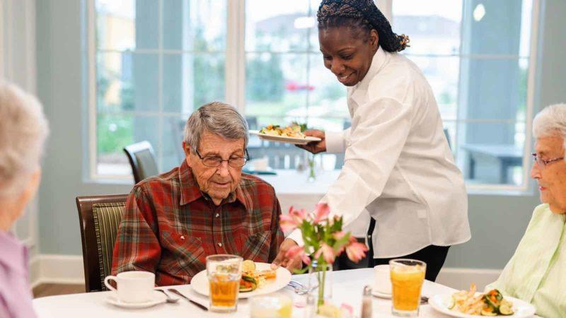 seniors-dining-table-waitress-serving-food