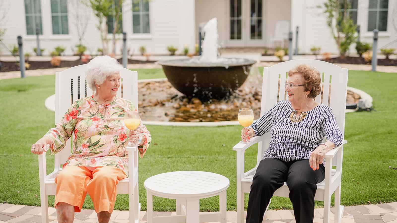 Two senior women seated in courtyard with drinks