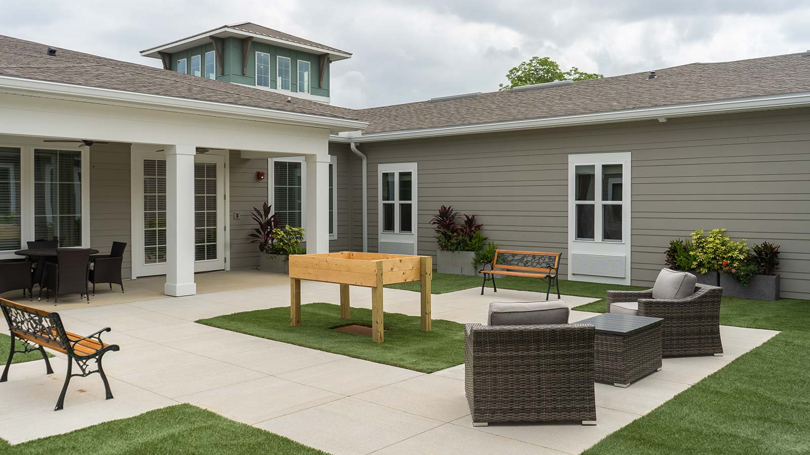 View Of Landscaped Courtyard With Outdoor Seating, Covered Patio And Raised Garden Beds