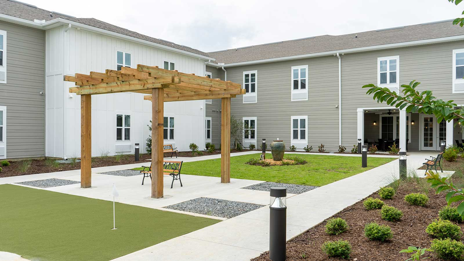 View of landscaped courtyard with outdoor seating and covered patio at The Canopy at Azalea Grove assisted living and memory care community in Valdosta, GA