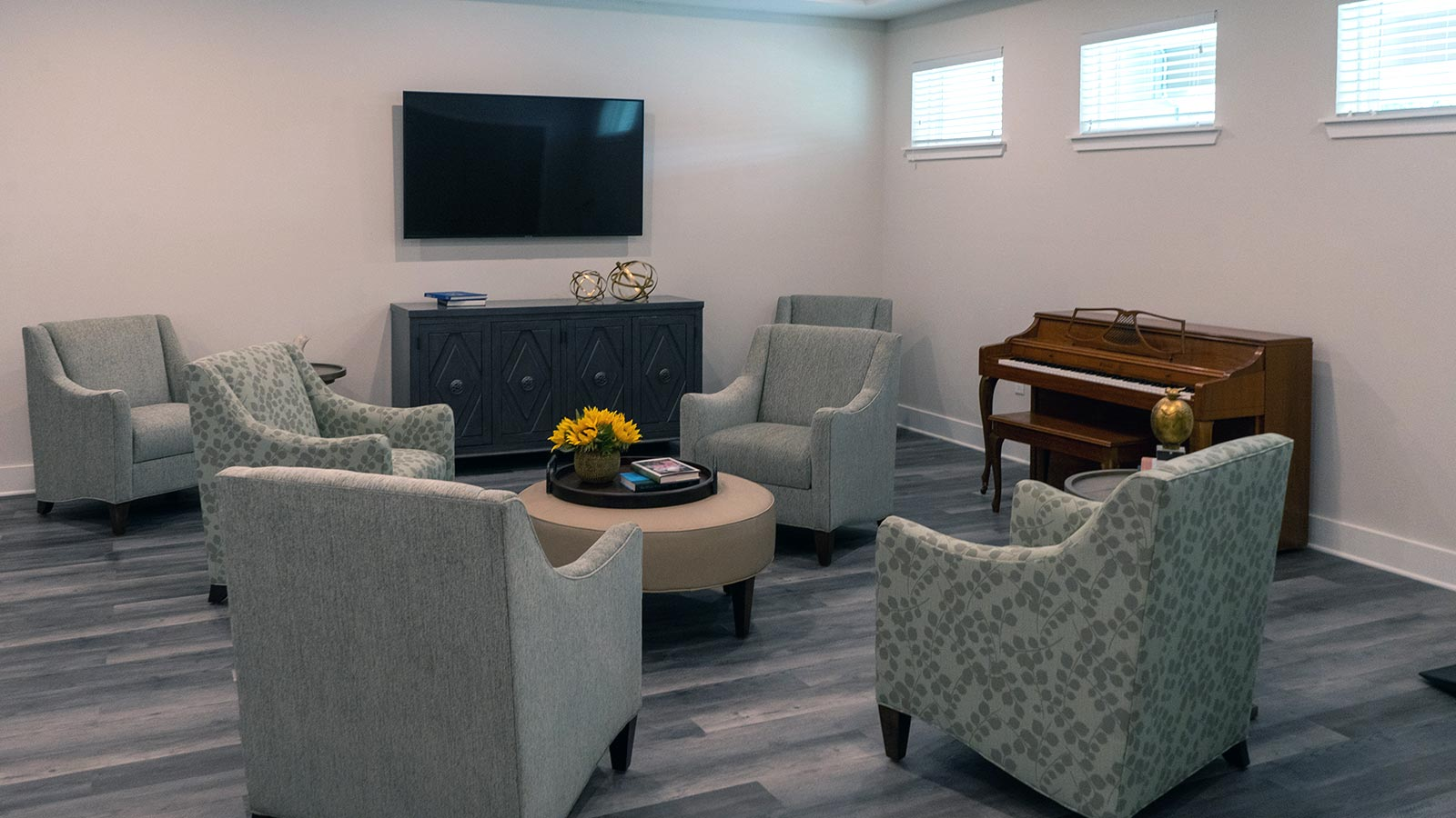 View Of Gathering Area With TV, Comfortable Chairs And Piano